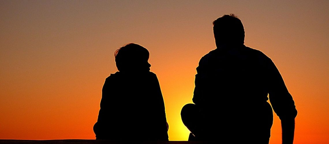 father and son enjoy sunset